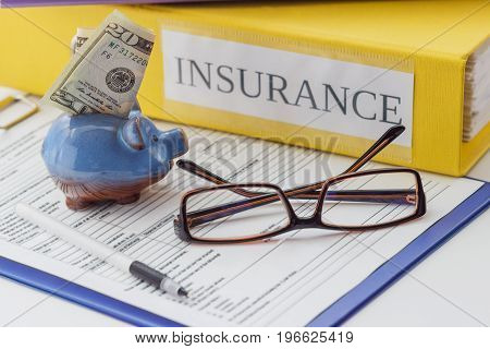 Clean Insurance Form, Folders, Pen, Piggy Bank And Glasses