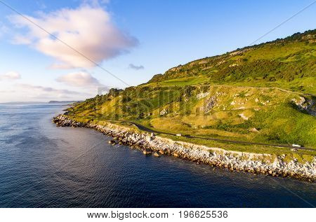 The eastern coast of Northern Ireland and Antrim Coast Road a.k.a. Giant's Causeway Coastal Route with cars. Aerial view at sunrise.