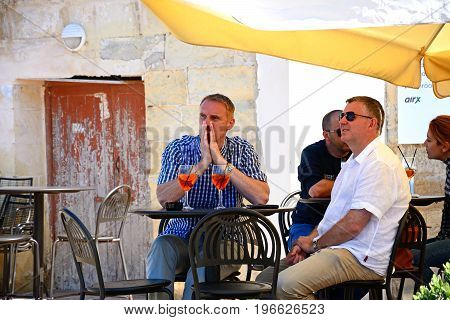 VITTORIOSA, MALTA - MARCH 31, 2017 - Tourists relaxing at a pavement cafe along the waterfront Vittoriosa Malta Europe, March 3, 2017.