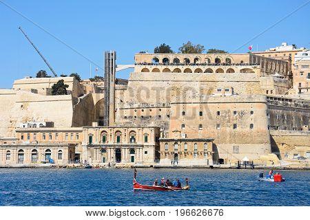 VALLETTA, MALTA - MARCH 31, 2017 - Tourists aboard a traditional Maltese Dghajsa water taxi with views towards Upper Barraka Gardens Valletta Malta Europe, March 31, 2017.