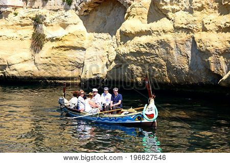 VITTORIOSA, MALTA - MARCH 31, 2017 - Passengers on board a traditional Maltese Dghajsa water taxi in an inlet alongside Fort San Angelo Vittoriosa Malta Europe, March 31, 2017.