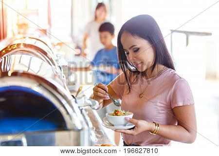 Portrait of beautiful thai asian women hand holding mush or boiled rice pork for thai style at buffet in restaurant Breakfast buffet self service in morning at hotel.