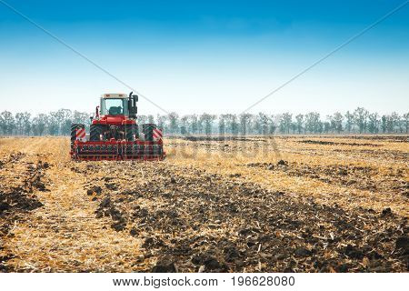 Modern tractor in the field with complex for the plowing. The concept of work in a fields and agriculture industry.