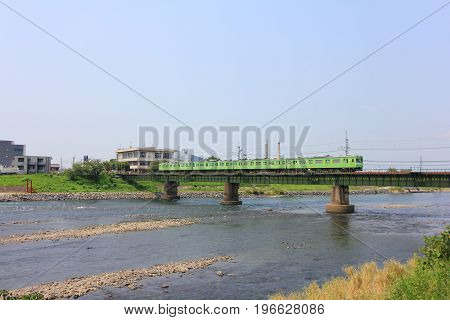 View of Uji river with the Uji Bridge local train houses in summer at Uji city near Kyoto Japan.