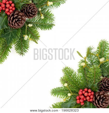 Christmas background border with holly, fir, ivy, mistletoe and pine cones on white.