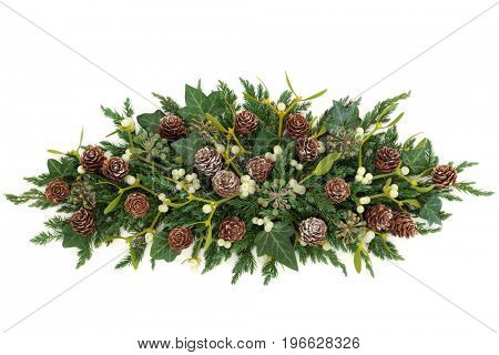 Winter greenery display with mistletoe, juniper fir, ivy and pine cones forming a centrepiece on white background.