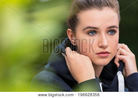 Beautiful girl teenager female young woman with blue eyes outside wearing dark blue hoody looking sad depressed or thoughtful