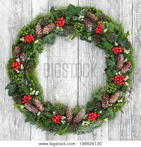 Christmas wreath decoration with holly, mistletoe, snow covered fir, blue spruce, ivy and pine cones on rustic white wood background.