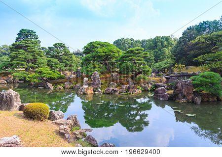 Ninomaru garden a traditional Japanese Zen garden in summer season with Bonsai trees stones pond and rock bridge. at Nijo Castle (Nijojo) famous historic site and tourist destination in Kyoto Japan.