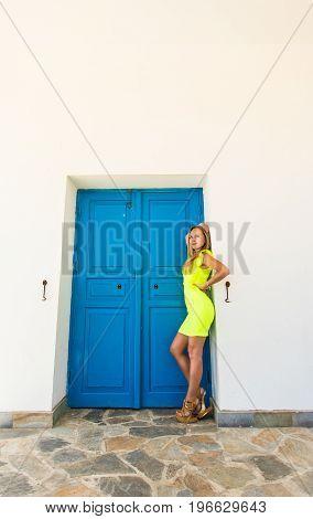 Young woman standing next to blue door of building