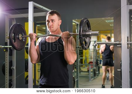 Muscular man with pulling up barbell in fitness training class indoors.