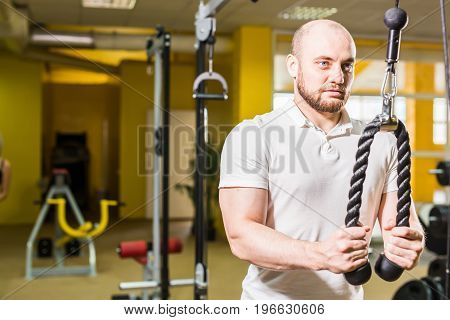 Exercise for triceps in the gym. Handsome power athletic man