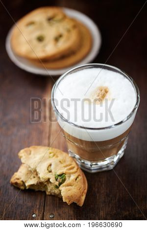 Glass of latte coffee and pistachio cookie on wooden background