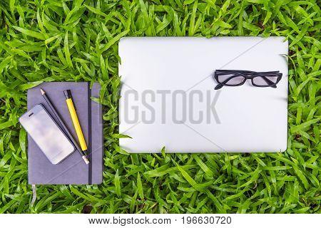 Business equipment on grass field Top view concept.