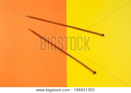 Pair of wooden knitting needles on colorful yellow and orange background