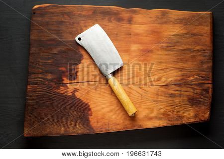 Chopping board with meat cleaver on dark wooden background.