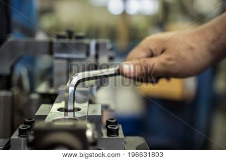 Worker is used Hexagonal screwdriver in factory