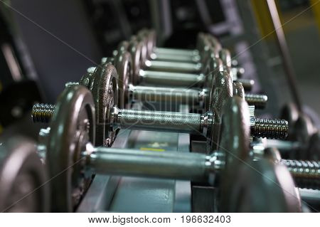 dumbbells in gym. Close up many dumbells in sport fitness centre.
