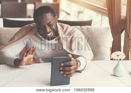 Distance communication. Delighted positive nice man holding a tablet and greeting his interlocutor while making a video call