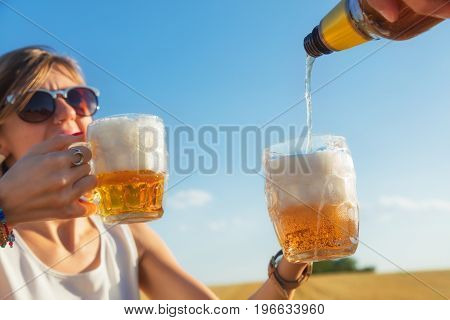 Happy girl holding beer glasses in a big wheat-field.