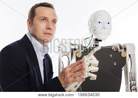 Looking forward. Creative curious admirable man working in his lab and running an examination on the robot while holding its hand