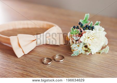 Pair of golden wedding rings peach colored bow tie and peony boutonniere lie on wooden surface. Traditional accessories of the groom at the wedding.