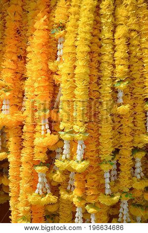 close up yellow marigold flower garland in public temple Thailand