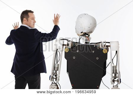 Projection on the wall. Handsome strategic talented inventor working on his latest invention in a lab while programming his robot and standing isolated on white background
