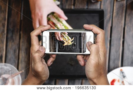 Taking food photo, food photography by smart phone, club sandwich with french fries on wooden table