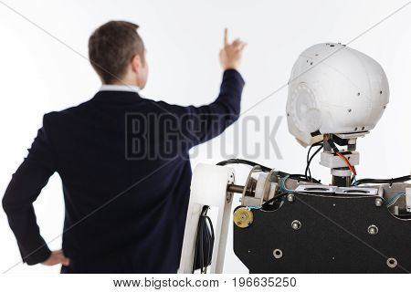 Innovative technologies. Young dedicated passionate man working in his laboratory and employing interactive screen for programming his robot