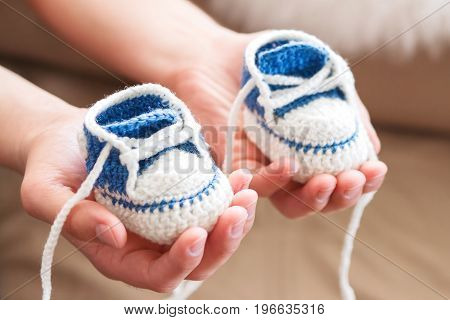 Little baby shoes. Handknitted first sneakers for boy or girl. Crochet handmade bootees in daddy's hands. Newly father presents knitted shoes.