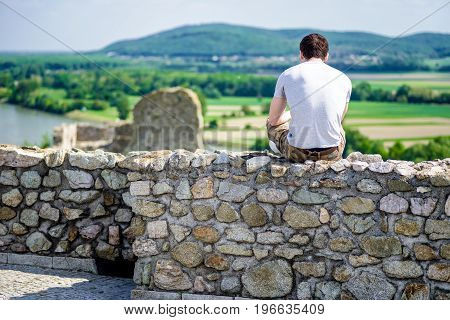 Man sitting and relaxing on ruins of Devin castle near city Bratislava Slovakia
