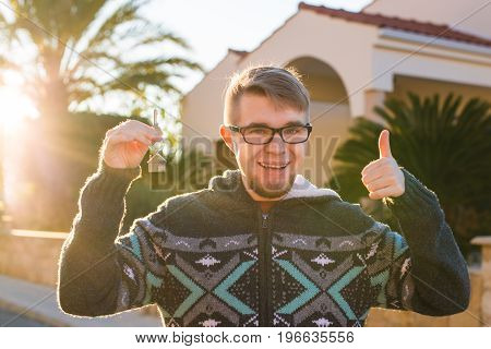 Portrait of a young man holding new house key and gesturing thumbs up