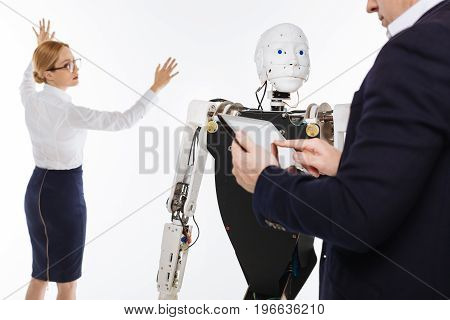 Computer mind. Energetic remarkable brilliant scientists using innovative technologies while programming the robot and running a number of tests