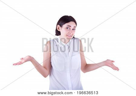 A shocked young business woman in a white blouse, isolated on a white background. An attractive and adult girl shrugs shoulders and spread out her hands in misunderstanding. A lady having problems.