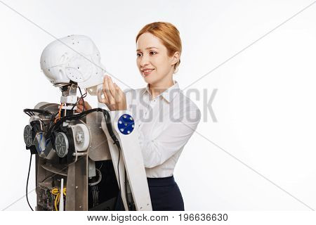 Masterpiece of the new era. Charming hardworking motivated woman giving the mechanisms final touches while working in a lab and finishing the looks of the robot