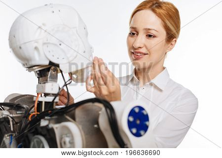 Precious creation. Young intelligent passionate scientist seeming fascinated with newest invention and studying it carefully while standing isolated on white background