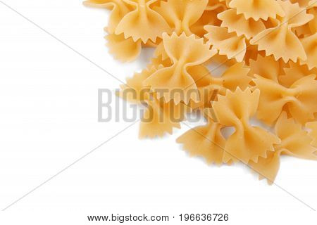 Top view of uncooked yellow farfalle, isolated on a white background. Typical Italian food pasta. Raw and hard farfalle pasta. Flour products. Macarons, noodle, pasta, and spaghetti.