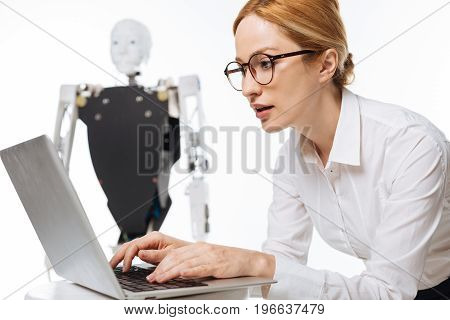Important task. Young passionate brilliant woman seeming fascinated while working on new project and developing artificial intelligence