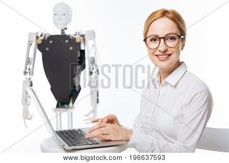 Fascinating science. Young emotional inspired woman writing an article about artificial intelligence while spending some time in a lab and running tests