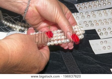Gemologist expert assesses the quality of pearls. Women's hands control quality with tools.
