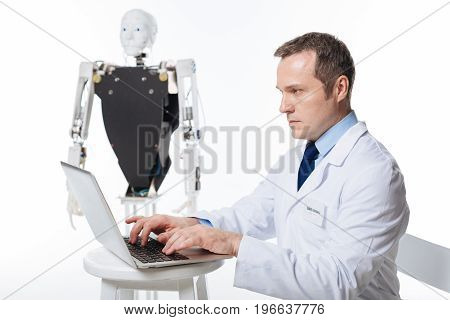 Aiming for success. Admirable dedicated intelligent scientist spending time in lab and developing software for the robot while using his laptop