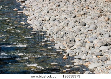 closeup of riverbed with grey pebbles and boulders
