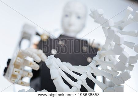 Just like humans. White complex mechanism with artificial intelligence reaching his hand for touching the DNA chain which representing the future of genetic engineering
