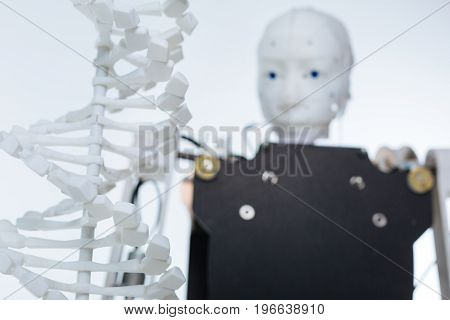 Same material and different purpose. Special white experimental equipment placed in front of the robot with artificial mind