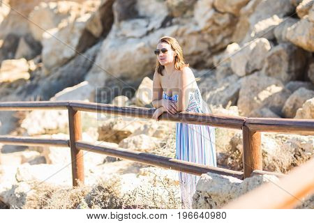 Loneliness, summer, nature and people concept - Young woman standing alone, relaxing and looking away.