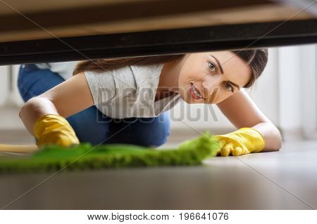 young woman in protective gloves cleaning floor under bed with mop. Housework, housekeeping and wet cleaning concept