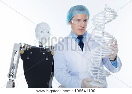 Decipher the codes. Passionate qualified charming scientist standing isolated on white background while examining DNA and doing science in a lab