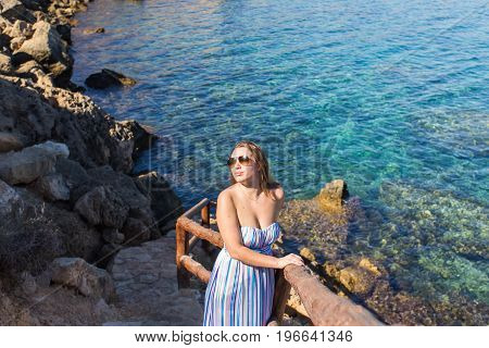 Beautiful lady in striped dress on rocky shore.