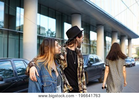 Stylish unfaithful young male hugging his fashionable girlfriend and gazing after another girl who just walked by them. People relationships romance love triangle jealousy and infidelity concept